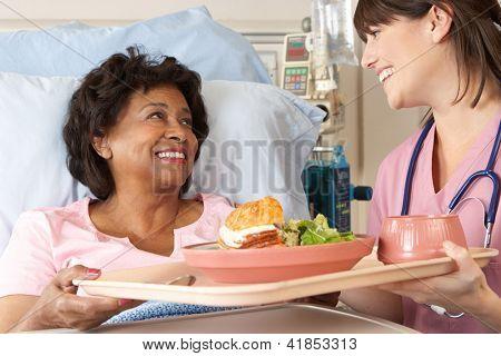 Nurse Serving Senior Female Patient Meal In Hospital Bed