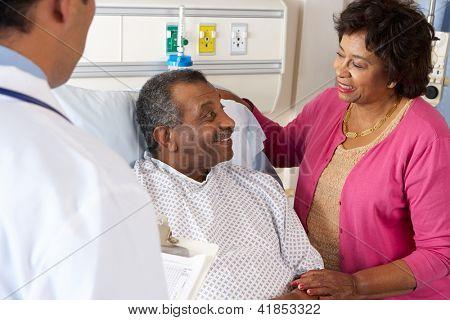 Doctor Talking To Senior Couple On Ward