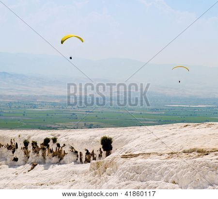 two parachutists on the background of the Travertine pools and terraces, Pamukkale, Turkey