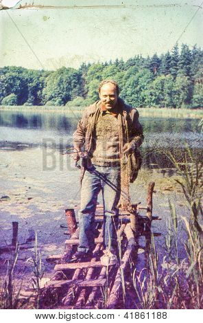 Vintage photo of fisherman at lakeside (seventies)