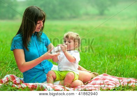 mother and daughter have picnic drinking water from bottle