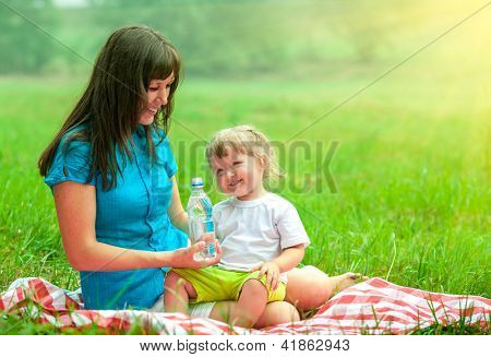 mother and daughter have picnic outdoor drinking water from plastic bottle