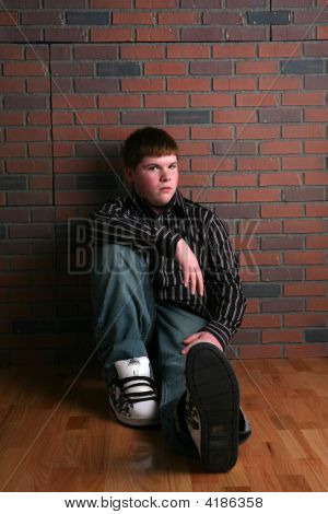 Teenage Boy Sitting On Floor