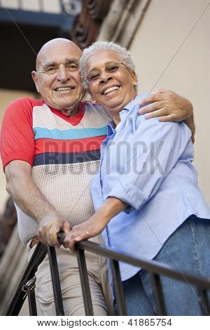 Portrait of a happy senior couple standing together by the railing