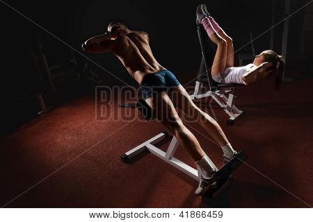 Young bodybuilder training his muscular back and woman working on her prelum on the bench in gym