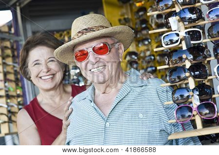 Portrait of happy senior Caucasian man trying sunglasses with woman at shop