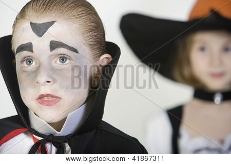 Closeup of a boy in vampire outfit with female friend in the background isolated over white background