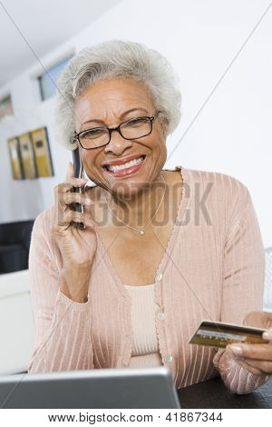 Portrait of happy African American senior woman using cell phone while holding credit card