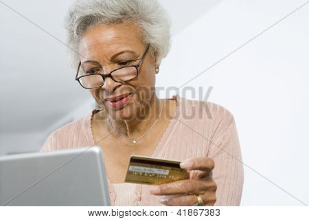 Senior African American woman shopping online using laptop and credit card