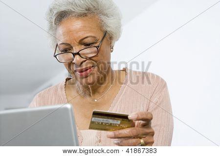Mujer afroamericana Senior de compras online con portátil y la tarjeta de crédito