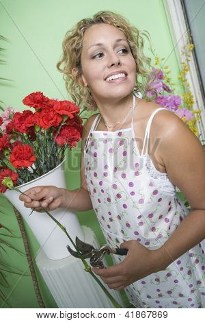 Happy female florist in apron trimming flowers with secateurs at shop