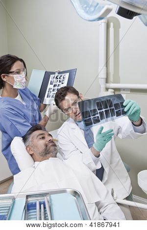 Nurse with male dentist explaining patient his x-ray reports in clinic