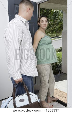 Young hispanic expectant couple looking at each other while leaving home