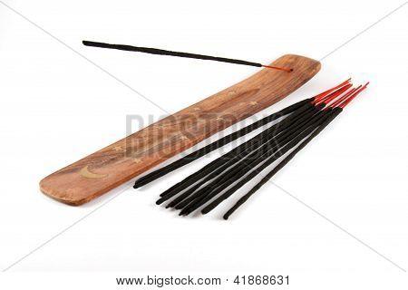 Varitas de incienso en el soporte de madera aisladas sobre fondo blanco
