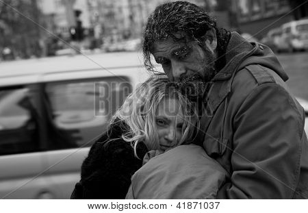 Black and white image of homeless couple embracing in city center