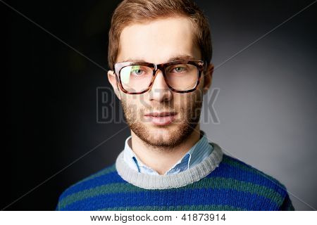 Portrait of attractive male in casual clothes and eyeglasses looking at camera