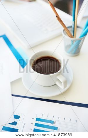 Vertical image of an office workplace with papers, stationary and a cup of coffee
