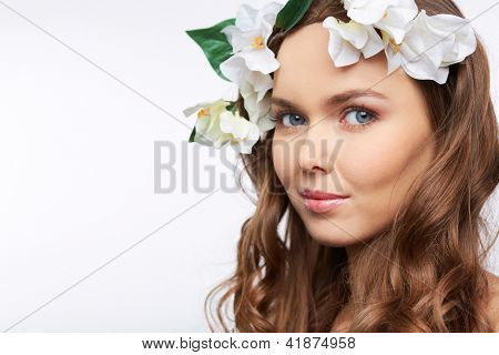 Isolated image of an attractive young woman with curly hair and flower decoration