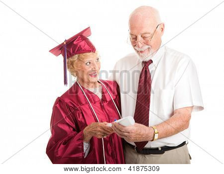 Senior woman graduating from college, proudly shows her diploma to her husband.  Isolated on white.