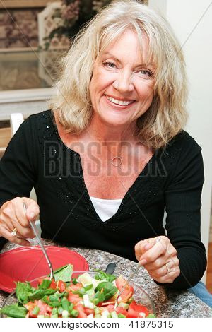 Beautiful healthy middle aged woman sitting down to eat a healthy green salad.