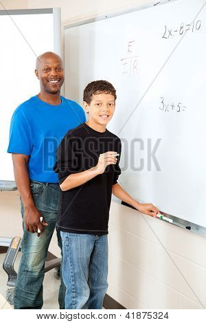 Handsome african-american teacher helps student at the board with math.