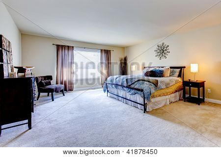 Large Bedroom With Beige Carpet And Black Bed.