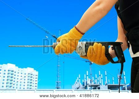 Construction worker building with drill on a building background