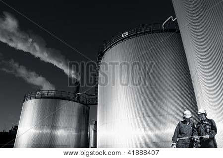 refinery workers with giant industrial storage towers, sunset picture.