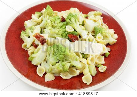 An Italian-style romanesco and pasta meal, cooked with chopped sun-dried tomatoes and topped with slivers of parmesan cheese. The romanescu cauliflower fllorets are parboiled then fried.