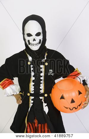 Preteen boy in grim reaper's outfit with pumpkin bucket isolated over white background