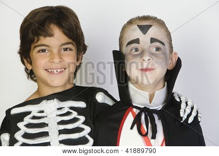 Portrait of two preteen male friends in Halloween outfit isolated over white background