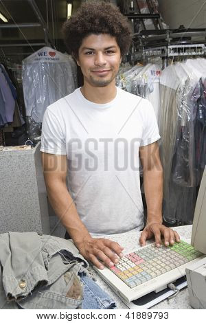 Portrait of a young mixed race man standing by checkout counter at dry cleaning store
