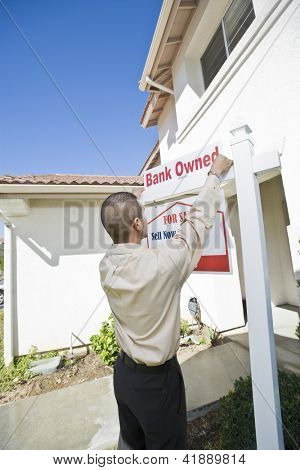Young hispanic man putting up foreclosure notice at house