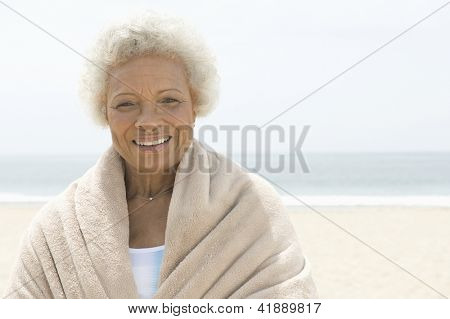 Portrait of a happy African American woman wrapped in towel with sea in the background