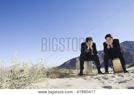 Full length of two bored businessmen sitting on briefcase in desert