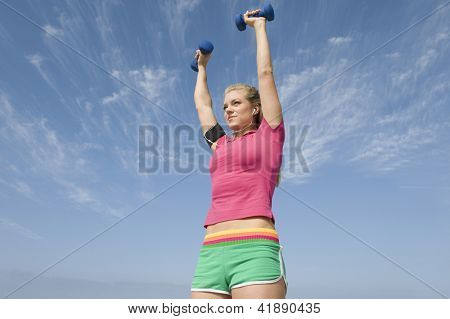 Low angle view of sporty young woman exercising with hand weights while listening music against sky