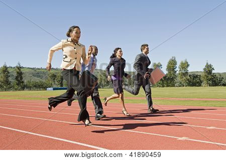 Full length of four business people running together on racing track