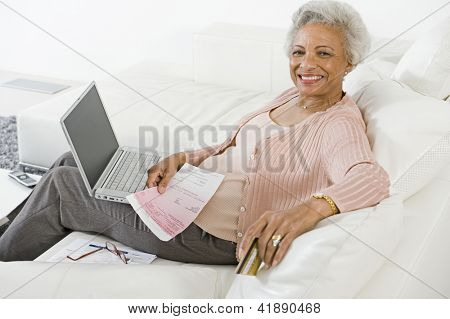 Happy African American senior woman making online payment of bills using laptop