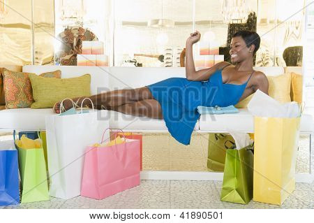 African American woman lying on sofa in a lavish clothing store with shopping bags on floor