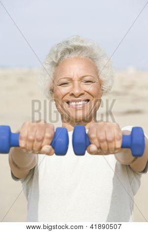 Portrait a happy African American senior woman exercising with two dumbbells at beach