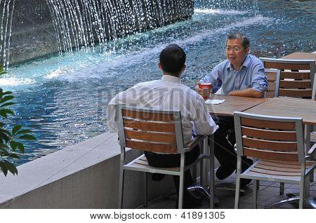 Two men meeting near fountain.