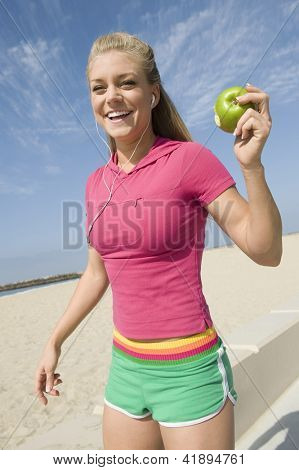 Portrait of jovial young woman in sportswear enjoying music while having green apple