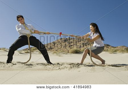 Full length of  business people playing tug of war in desert