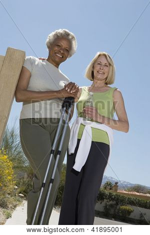 Low angle view of an African American senior woman standing with friend in park