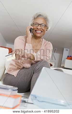 Cheerful African American senior woman using cell phone while holding credit card