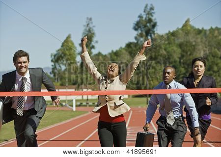 Female businesswoman cheering with competitors running on the racing track