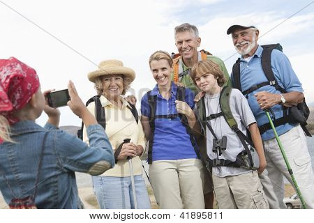Little girl taking picture of happy Caucasian family on vacation against sky