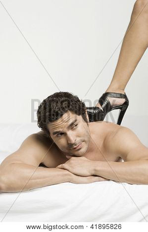Man lying on bed with woman's leg on his bare back