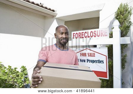 An African American sad man carrying cardboard box while moving out of the house