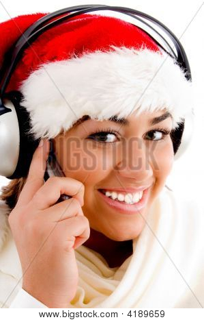 Beautiful Woman Wearing Christmas Hat And Enjoying Music